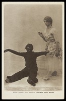 view Harold Chapman in drag poses with Mark Leslie dressed as a Golliwog, in an act for the Bow Bells. Photographic postcard, 191-.