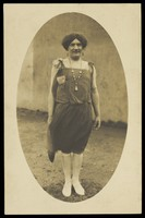 view An amateur actor in drag, wearing a flapper dress and white footwear. Photographic postcard, 1925-1928.