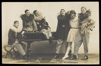 view Soldiers, one in drag, performing in the concert party for Mesopotamia, posing around a piano. Photographic postcard by Hana Studios, 191-.