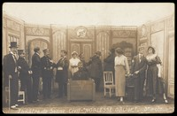 """view Prisoners of war, some in drag, posing on stage during a crowded scene of """"Noblesse oblige""""; at Sennelager prisoner of war camp in Germany. Photographic postcard, 191-."""