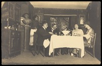 view Belgian prisoners of war, some in drag, sit at a table within a very detailed stage set at Friedberg camp, Germany. Photographic postcard, 191-.