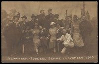 view Belgian prisoners of war, some in drag, pose on stage for a group portrait; at Sennelager prisoner of war camp in Germany. Photographic postcard, 1918.