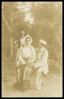 view Three actors, one in drag, posing in a tableau. Process print, 191-.