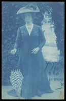view An man in drag, wearing a large hat and veil, posing in a garden. Colour process print, 191-.