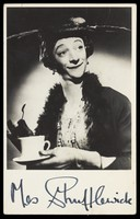 view Mrs. Shufflewick (Rex Jameson), in drag character, holding a cup of tea. Photograph, ca. 1955.