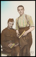 view Two Belgian soldiers cleaning their uniforms. Colour photographic postcard, 192-.