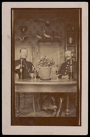 view Two military officers in uniform sitting at a table in a domestic kitchen. Photographic postcard, 191-.