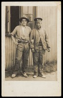 view Two soldiers stand arm-in-arm outside a building of corrugated metal (barracks?). Photographic postcard, 191-.