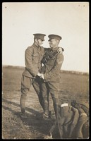 view Two soldiers embrace in a field. Photographic postcard, 191-.