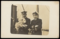 view Two naval officers posing with a dog. Photographic postcard, 192-.