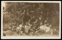view Soldiers relaxing in a field. Photographic postcard, 191-.