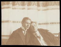 view Two men resting close to one another, wearing formal attire. Photograph, 1910.