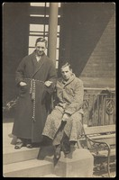 view Two men wearing dressing gowns sitting arm-in-arm on a terrace. Photographic postcard, 192-.
