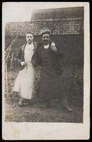 view Two men, standing together in a garden, one with his arm around the other. Photographic postcard, 1907.