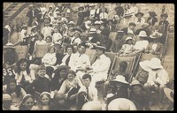 view Families sitting in deckchairs, with two men in naval uniforms embracing in the centre. Photographic postcard, 191-.