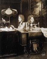 view Daisy and Violet Hilton, conjoined twins, one sewing, one using a typewriter. Photograph, c. 1927.