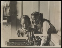 view Rubber beauty masks, worn to remove wrinkles and blemishes; modelled by two women at a typewriter. Photograph, ca. 1921.