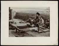 view Benares, India: a fakir sitting on a bed of nails. Photograph by R.C. Mazumdar, ca. 1900 (?).